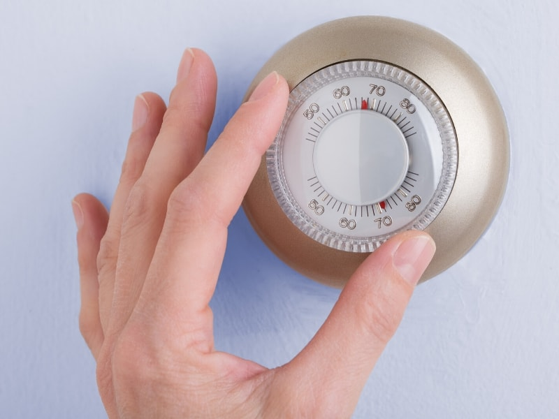 hand touching thermostat on wall